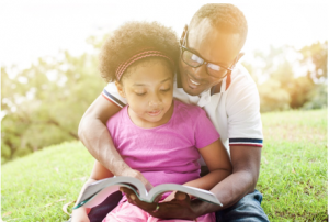 young girl sitting outside with her dad reading a book